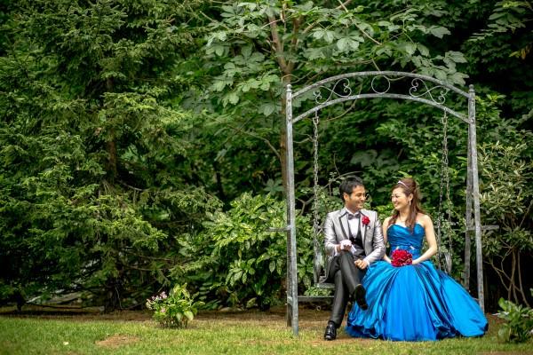 ジャルダンドゥボヌールのガーデンのブランコに座ったグランマニエのカラードレスを着た花嫁